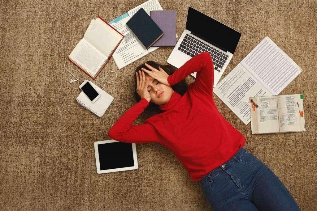 Tired student girl lying on the floor